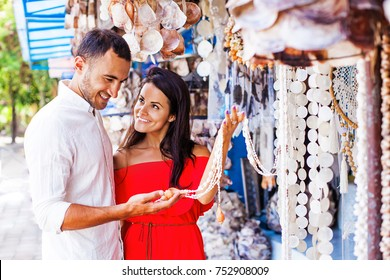 beautiful couple choosing exotic seashell accessories in market