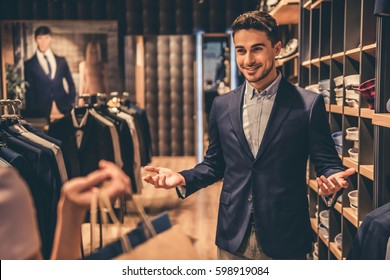Beautiful couple is choosing formal suit and smiling while doing shopping in the male store