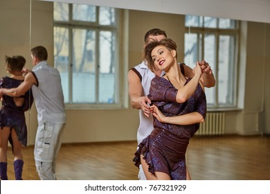 beautiful couple dancing bachata in dance studio