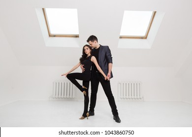beautiful couple dancing bachata on white background in studio