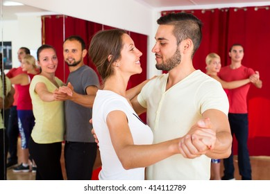 Beautiful couple dancing waltz in dancing school looking in each other's eyes