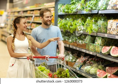 Beautiful couple do shopping with trolley and choosing products in supermarket. Bearded man and woman with braids standing in vegetable section. Customers smiling and looking at shelves.