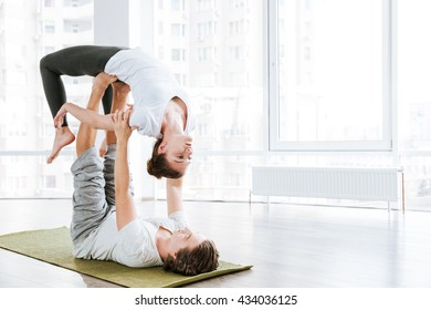 Beautiful couple doing stretching exercises in yoga studio together