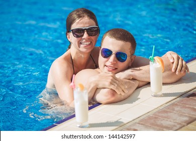 Beautiful couple drinking cocktails, hugging and kissing in the swimming pool on tropical resort