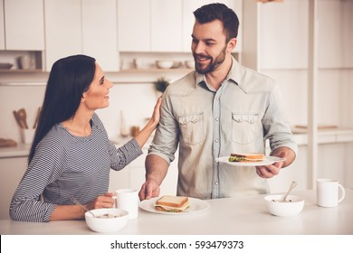 Beautiful couple is eating sandwiches, talking and smiling while sitting in kitchen at home