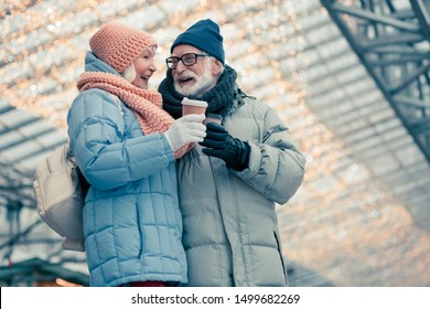 Beautiful couple of elderly people in warm winter clothes having a walk with cups of coffee. Illumination behind their backs