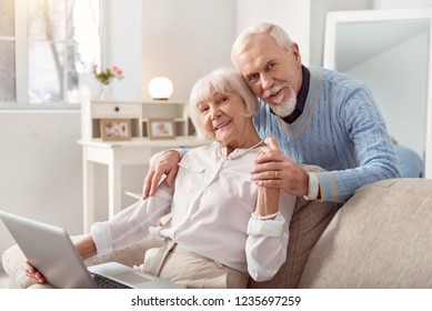 Beautiful couple. Elderly beautiful couple spending weekend while watching photos at the laptop