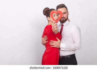 Beautiful couple embrace with passion, holding red heart. Indoor, studio shot, isolated on gray background