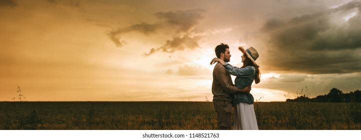 beautiful couple embracing on meadow at sunset