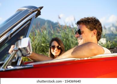 Beautiful couple enjoying in a convertible car ride
