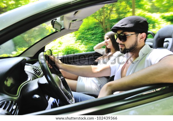 Beautiful couple enjoying nature in a sports car
