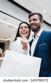 Beautiful couple enjoying in shopping mall or center. They standing in front of huge modern store, smiling and looking at side while holding shopping bags. Shoot from below.