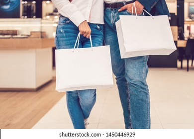 Beautiful couple enjoying in shopping mall or center. They standing in front of huge modern store and holding shopping bags. Shoot from below.