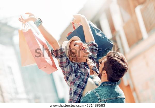 Красивая пара наслаждается покупками вместе в городе.