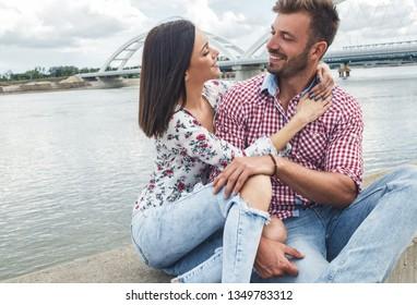 Beautiful couple enjoying time together outdoor, beautiful young woman hugging her boyfriend.