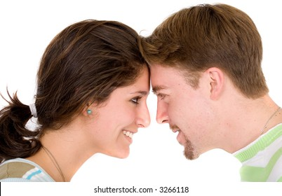 Beautiful couple face to face looking at each other smiling over a white background