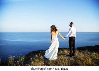 Beautiful couple in field, lovers or newlywed posing on sunset with perfect sky. Real emotions