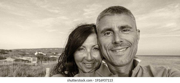 Beautiful couple in the forties smiling on the beach making a selfie at sunset.
