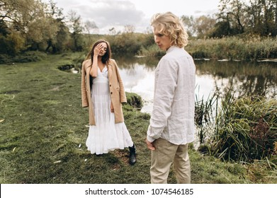 A beautiful couple in free clothes walks in the lawn near the lake on a sunny summer day