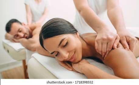 Beautiful couple getting a back massage, weekend spa for couple. Beautiful mixed race woman and man relaxes while back massage