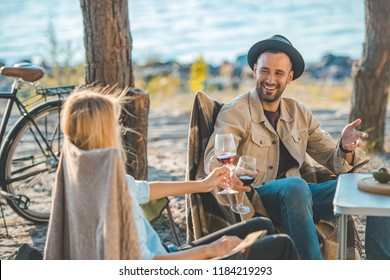 beautiful couple with glasses of wine talking during a picnic near sea