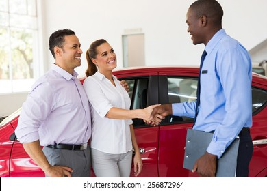 beautiful couple handshake with car salesman after purchasing a car