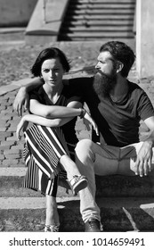 Beautiful couple of handsome bearded man hipster and pretty girl young brunette woman sit on stone stairs on sunny day