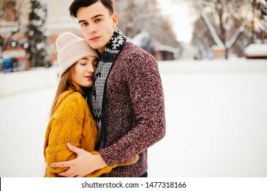 Beautiful couple have fun in a ice arena. Elegant girl in a yellow sweater.