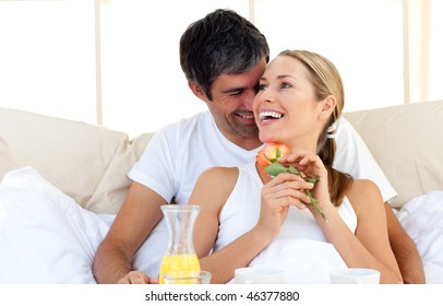 Beautiful couple having breakfast lying in the bed at home