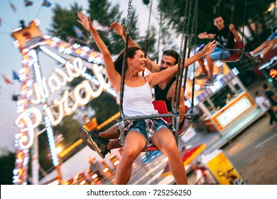 Beautiful couple having fun at luna park. Soft focus, high ISO, grainy image.