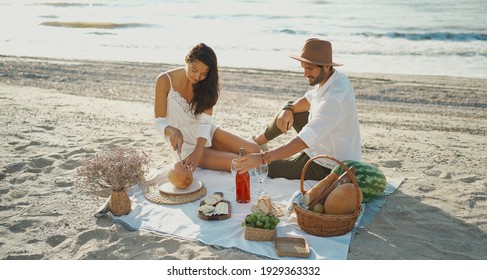 Beautiful couple having romantic breakfast with lots of tasty food and wine, sitting on piknic planket at beach with ocean view