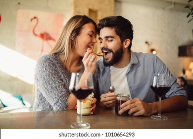 Beautiful couple having romantic moments in cafe, girl feeding her boyfriend with cake in cafe, drinking wine and celebrating Valentine's day.