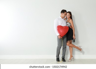 Beautiful couple with heart shaped balloon near light wall, space for text