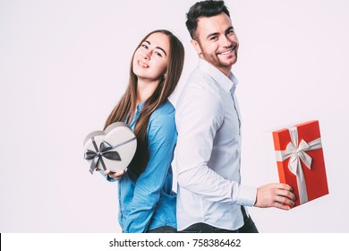 Beautiful couple holding gifts and looking at camera isolated. To give presents.