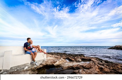 Beautiful couple hugging in the background of the sea on the coast of sea with cloudy sky