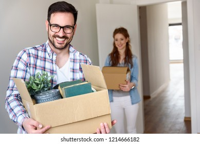 Beautiful couple just moving into new apartment holding boxes