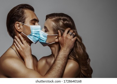 Beautiful couple kissing with surgical masks. Love during quarantine of coronavirus pandemic conception. Close up studio portrait. Copy, empty space for text