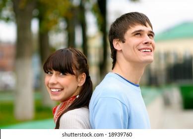 Beautiful couple laugh, looking in dark blue sky.