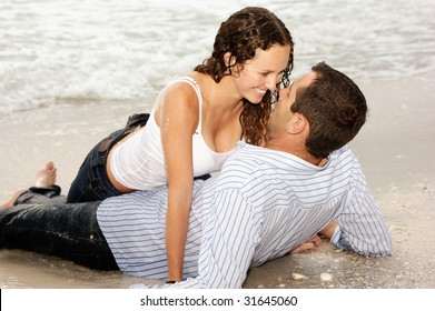 Beautiful couple laying on the beach looking into each others eyes, smiling and happy.