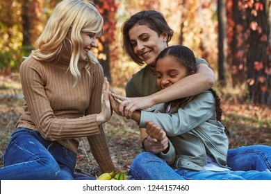 A beautiful couple of lesbian ladies having fun in the park with their adopted teenage daughter. The young family sitting on the ground, playing patty-cake, laughing. Autumn trees in the background.