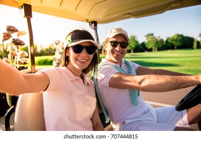 Beautiful couple is looking at camera and smiling while driving a golf cart