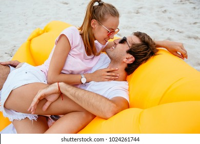 Beautiful couple looking to each other with love while resting on air sofa. On the beach. Dressed in t-shirts and shorts, in sunglasses.