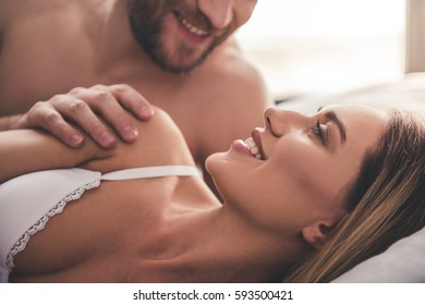 Beautiful couple is looking at each other and smiling while lying together in bed at home