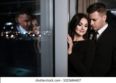a beautiful couple in love in a black dress and a classic costume are nestled near the window with the reflection of the night city with closed eyes