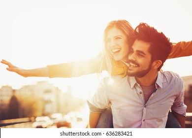 Beautiful couple in love cuddling while enjoying beautiful urban sunset together