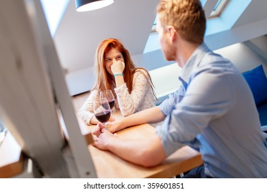 Beautiful couple in love drinking wine at home and talking casually