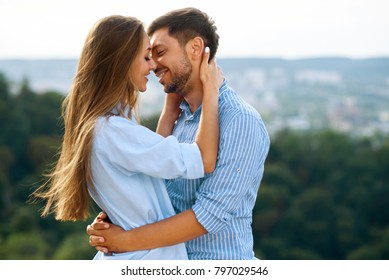 Beautiful Couple In Love Embracing Each Other In Nature. Portrait Of Happy Woman And Handsome Young Man In Stylish Clothes Hugging And Enjoying Date Outdoors. Romantic Relationship. High Resolution.