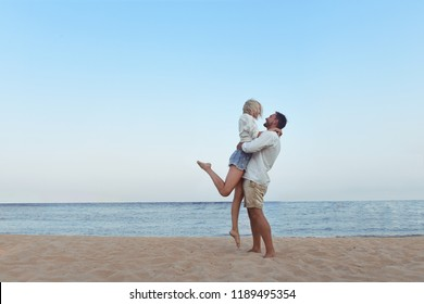 beautiful couple in love enjoying their hawaii vacation looking beach view. Cute blonde woman and handsome bearded man in white shirts standing on a sand hugging, holding hands, watching sea side.