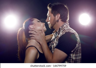 Beautiful couple in love flirting. The girl wants to kiss a guy. Black background