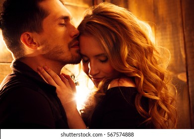 Beautiful couple in love hugging against the background of glowing lights. Studio portrait photo of a girl blondes and a guy with short hair. Valentine's day. Loving married couple. Family happiness